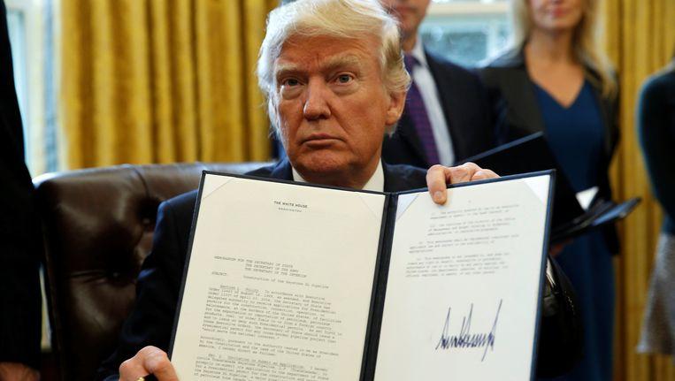 Trump houdt het decreet omhoog dat hij dinsdag heeft ondertekend, aangaande de aanleg van twee omstreden oliepijpleidingen. Beeld REUTERS