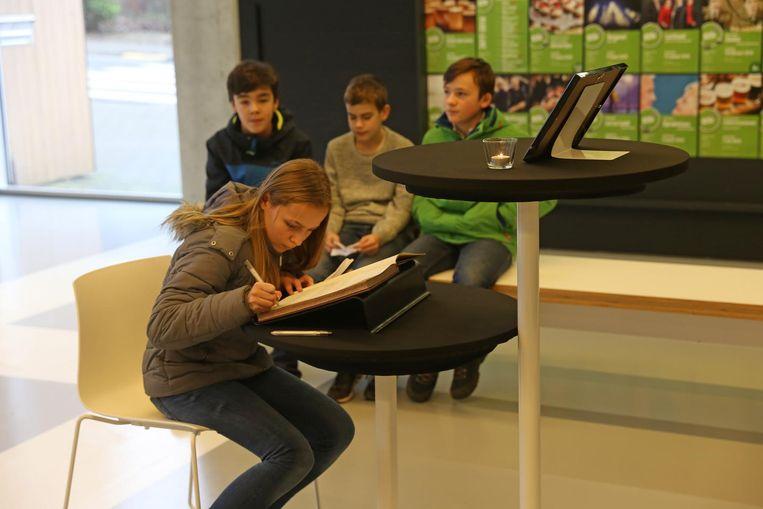 Klasgenootjes van Lies' kinderen tekenen het rouwregister in cultuurcentrum 't Oud Gasthuis.