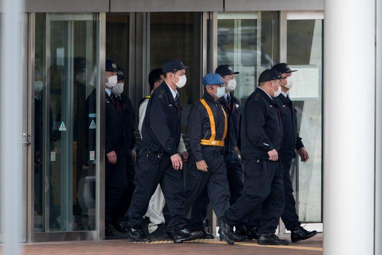 Na drie maanden voorhechtenis kwam Carlos Ghosn (jas met oranje strips) op 6 maart 2019 vrij op borg. Vanaf dan had hij huisarrest. Beeld AFP
