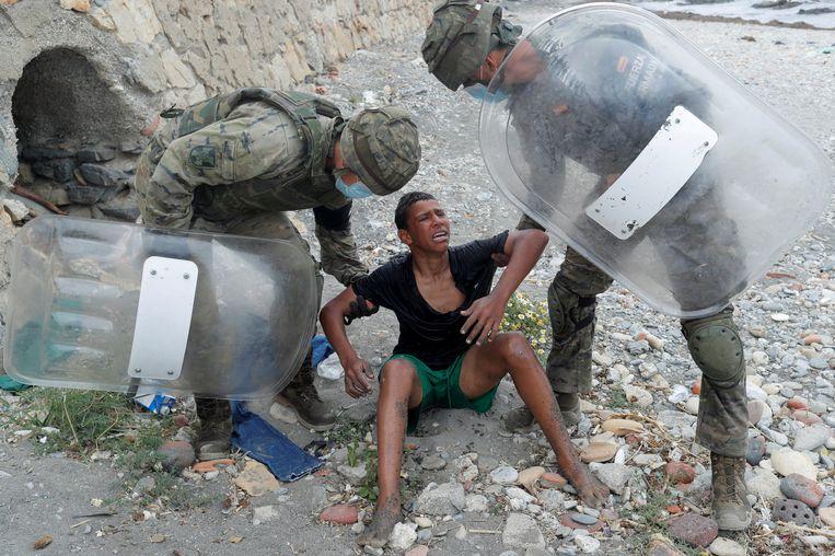 Een Marokkaanse jongen die de grens is overgekomen naar de Spaanse enclave Ceuta wordt door Spaanse soldaten overeind geholpen.  Beeld REUTERS
