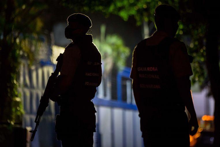 Leden van de Nationale Garde vrijdagavond bij het hoofdgebouw van de krant El Nacional in de Venezolaanse hoofdstad Caracas. Beeld EPA