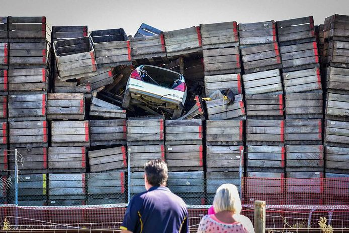 De auto van de man belandde tien meter hoog in een stapel kratten.