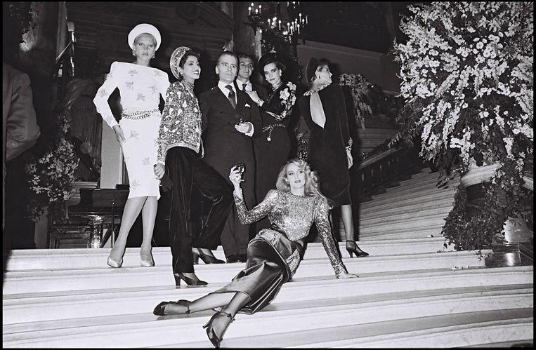 Karl Lagerfeld omringd door zijn modellen (Jerry Hall liggend op de trap) voor de Chanel herfst-winter collectie van 1985-1986.  Beeld Getty Images