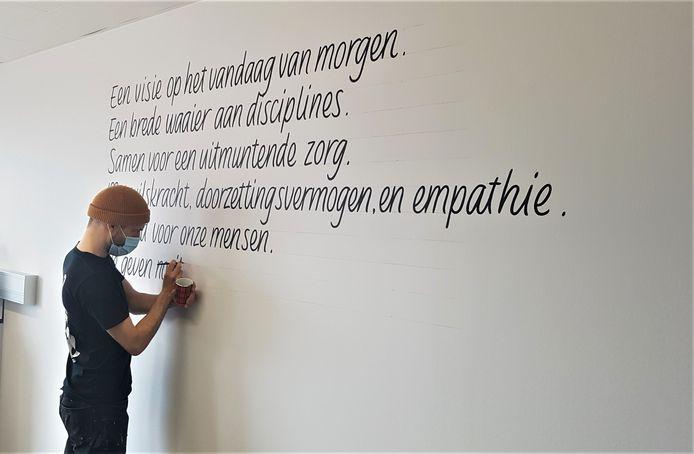 Woordkunstenaar Pieter Boels schildert verspreid over het hele ziekenhuis flarden uit de beloftetekst op de muren.