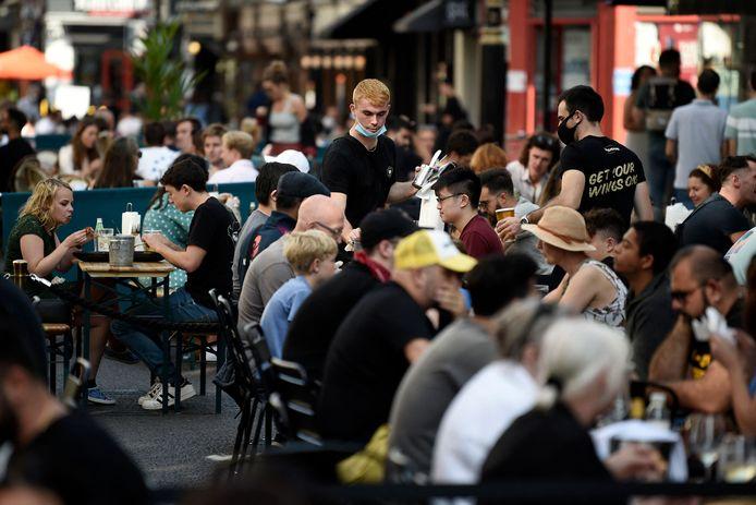 Mensen genieten van een terrasje in Soho, Londen.