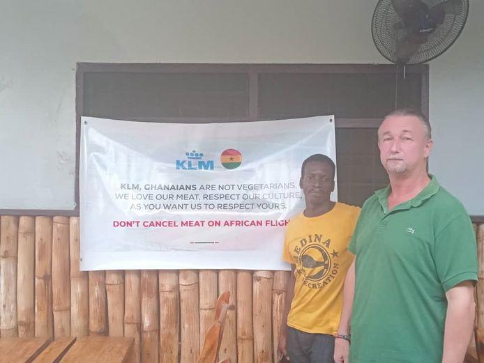 Nico van Staalduinen met een van de spandoeken bij hem thuis in Ghana.
