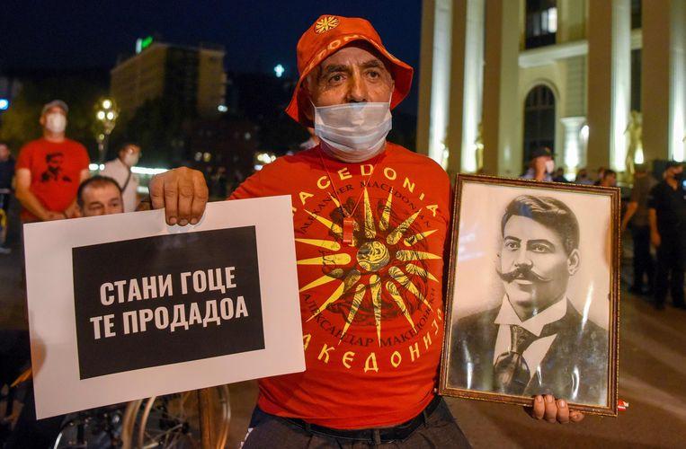 Een Macedoniër demonstreert in september tegen de regering in Skopje. Hij draagt een foto van de historische held  Gotse Deltsjev met de tekst 'Sta op Gotse, ze hebben je verkocht'.  Beeld AFP