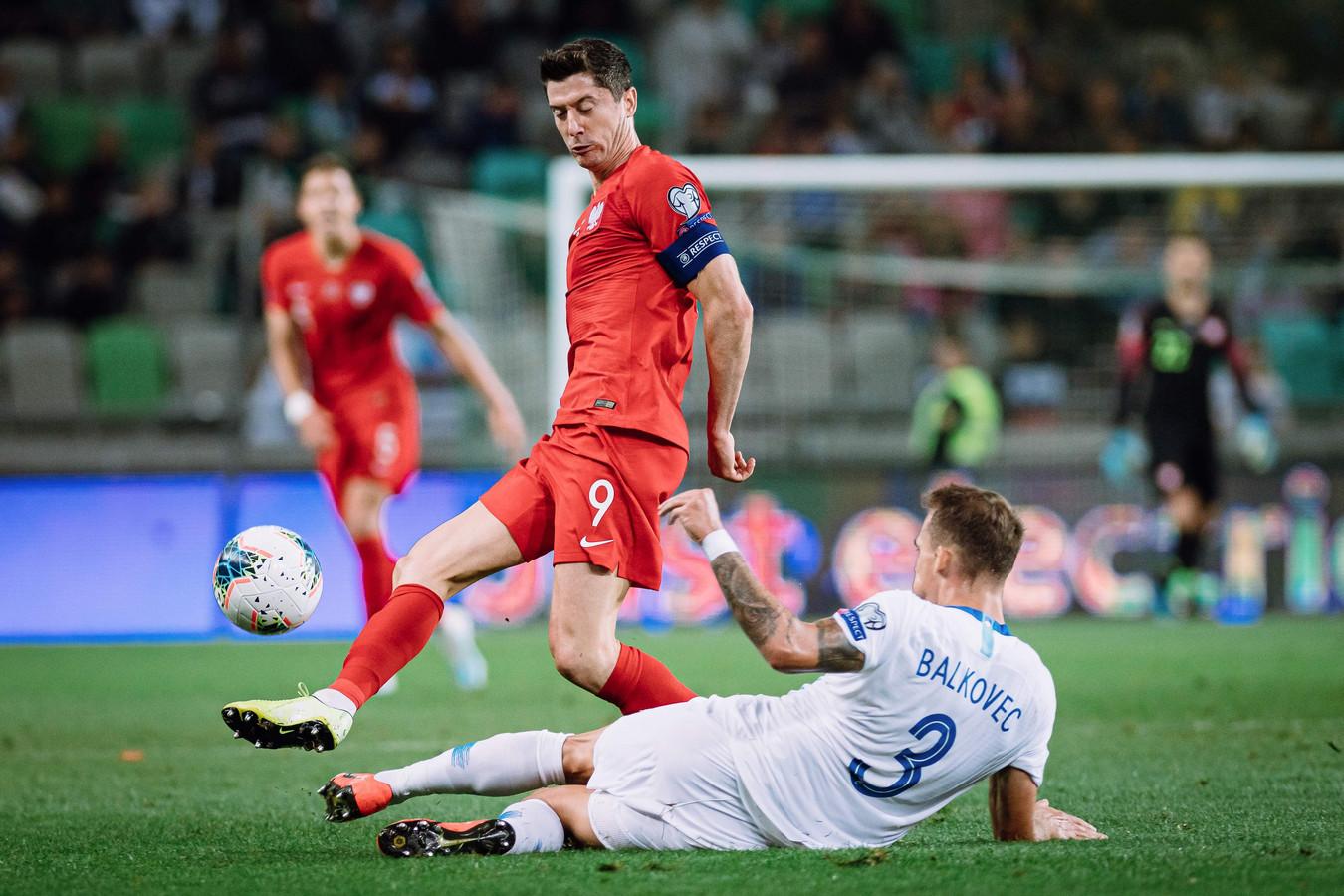 Robert Lewandowski van Polen in duel met Jure Balkovec van Slovenië.