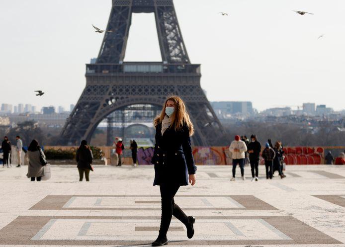 Vrouw met mondmasker aan de Eiffeltoren