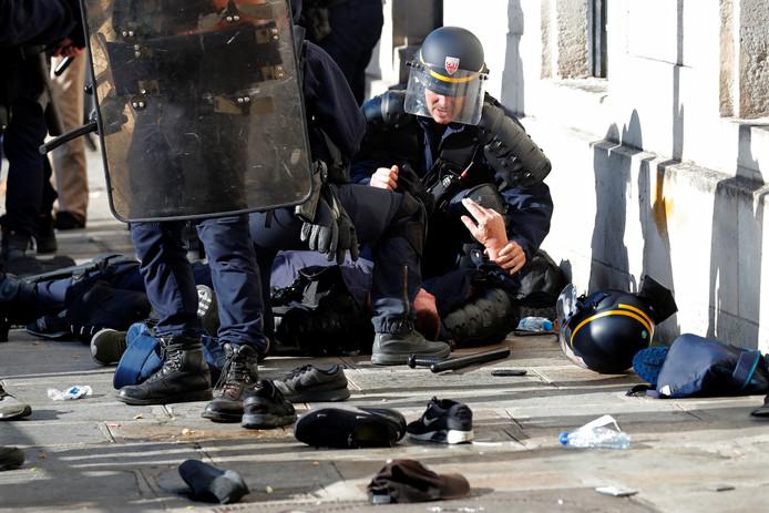 Een lid van de oproerpolitie krijgt medische verzorging na een confrontatie met de migranten