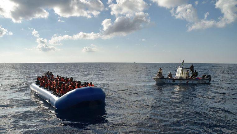 De Libische kustwacht nadert een rubberboot met migranten. Beeld Andreas Solaro / AFP