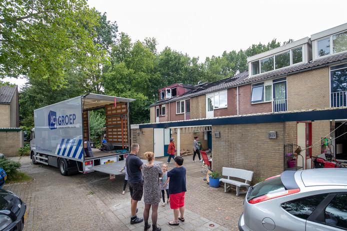 Bewoners van de onbewoonbare woningen halen spullen uit hun huizen.