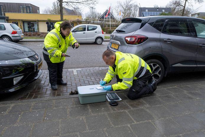 Vrijwilligers van de Dierenambulance lezen bij een aangereden kat de chip uit zodat ze het baasje kunnen traceren.