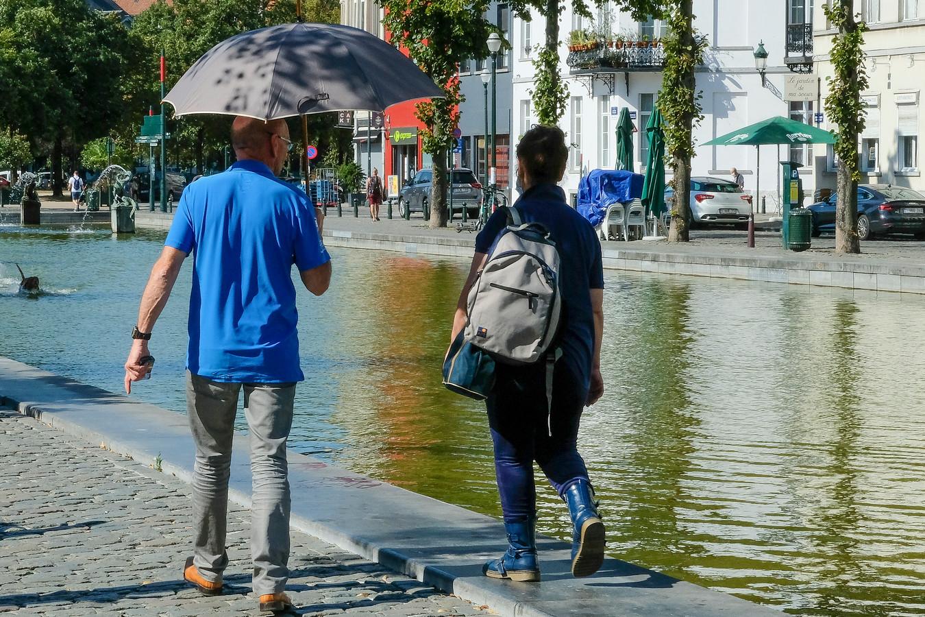 31 juli 2020: met een paraplu beschutting zoeken tegen de zon. Zo'n hitte lijkt er de komende maand niet in te zitten in onze omgeving.