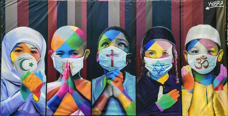 Met zijn muurschildering 'Coëxistentie' verbeeldt de Braziliaanse kunstenaar Eduardo Kobra kinderen van verschillende religies die een mondkapje dragen in de strijd tegen covid-19.   Beeld AFP