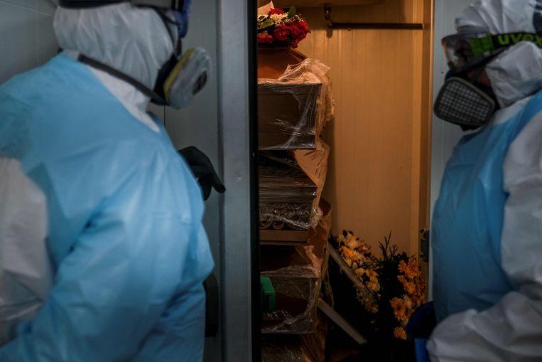 Uitvaartmedewerkers in een mortuarium in Amadora, een buitenwijk van Lissabon.  Beeld AFP