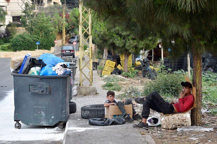 Syrische jongenes zitten bij een vuilniscontainer in Beiroet. Volgens UNHCR leven er momenteel anderhalf miljoen Syriërs in Libanon.