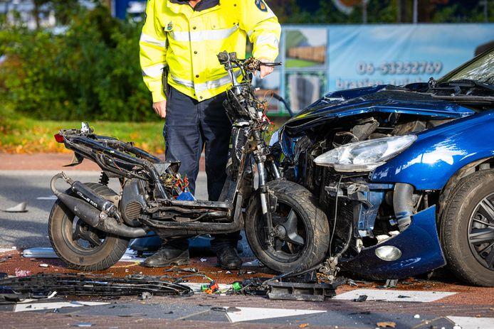 De klap van de aanrijding was zo fors, dat de scooter in delen op het wegdek belandde. Ook de auto liep forse schade op.