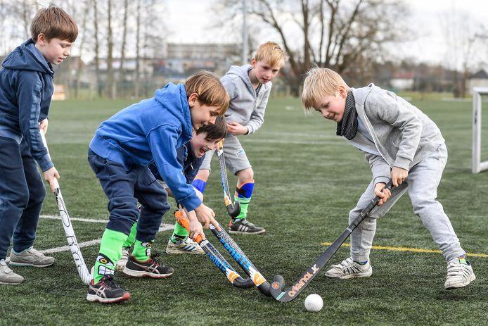 Enkele kinderen leven zich uit tijdens een wedstrijdje hockey in Dendermonde.