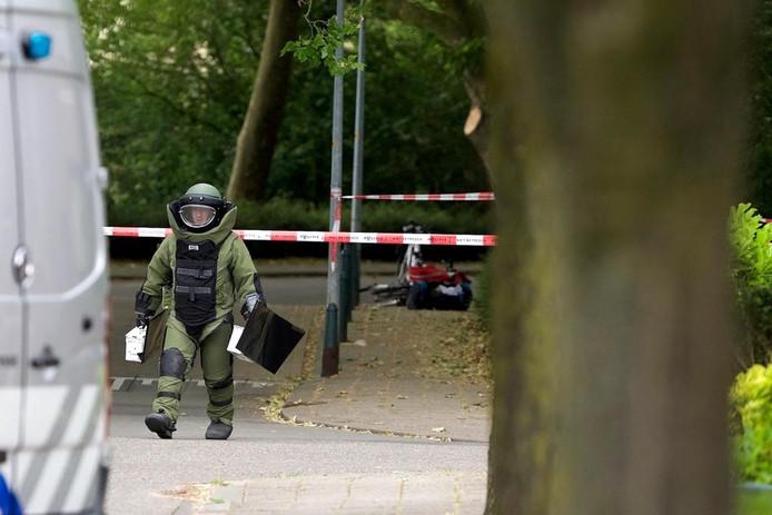 Een medewerker van de EOD loopt weg van de bomtas in Doesburg, die op de achtergrond is te zien.