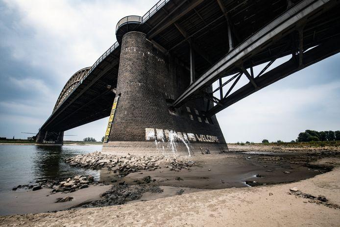 Onbekenden hebben de tekst 'Refugees welcome' onder de Nijmeegse Waalbrug met witte verf beklad.