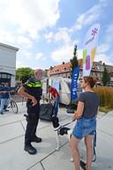 Een buurtbewoonster knoopt een gesprek aan met politieman Marco van Zanten, bij de mobiele meldpost tegen drugsoverlast.