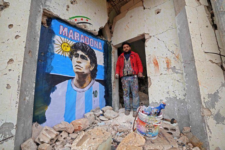 Syrische schilder Aziz Asmar bij zijn muurschildering van Maradona. Beeld AFP