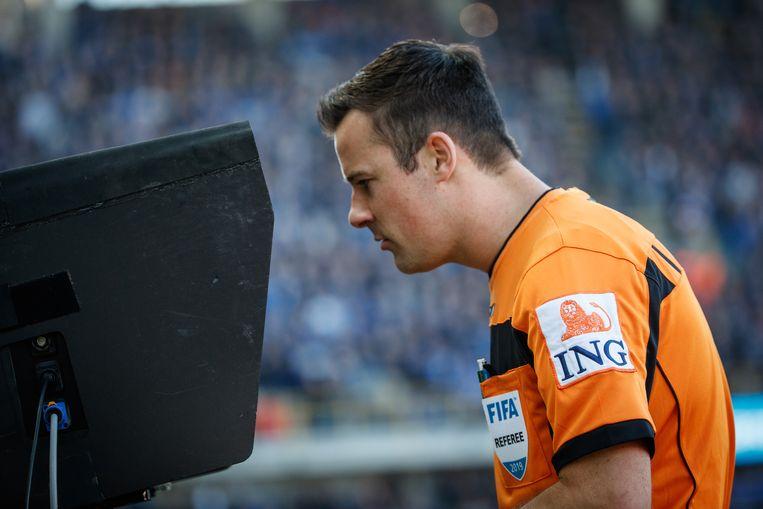 Scheidsrechter Bram Van Driessche kijkt naar een herhaling op de VAR. Hoe worden de voetbalrechten straks verdeeld? Dat valt af te wachten.  Beeld BELGA