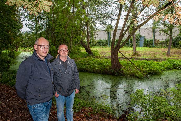 Buurtbewoners Peter van Gameren en Martijn Prang (is de langste van de 2) op de groene geluidswal met op de achtergrond de muur waar achter het verkeer op de A12 raast.