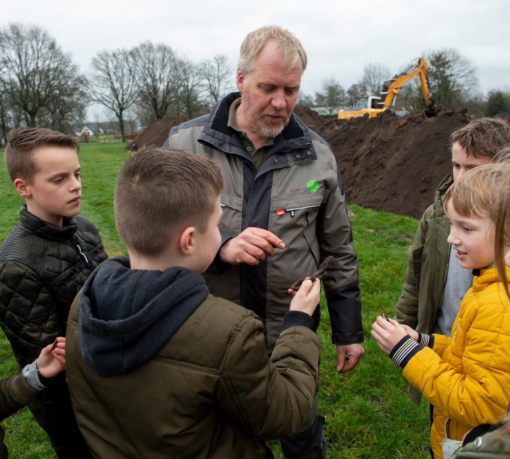 Archeoloog Peter Wemerman vertelt de kinderen van de Prinses Julianaschool in Lieren uit wat ze hebben gevonden.
