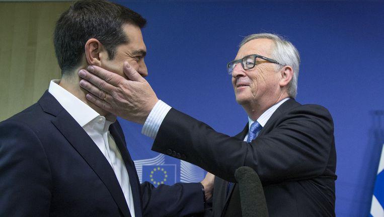 Alexis Tsipras krijgt een vriendelijke klets in zijn gezicht van Commissievoorzitter Juncker. Beeld REUTERS