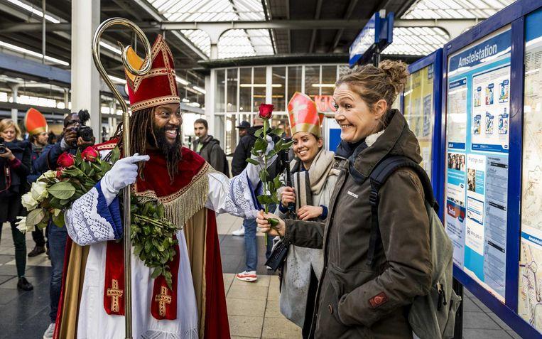 2016-11-05 11:57:36 AMSTERDAM - De Nieuwe Sint (Patrick Mathurin) deelt rozen uit aan reizigers op een metrostation tijdens zijn intocht in Amsterdam. ANP REMKO DE WAAL Beeld anp