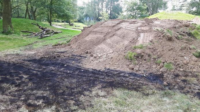De kruiptunnel is met zand afgedekt. Op de voorgrond het door de vlammen zwartgeblakerde gras.