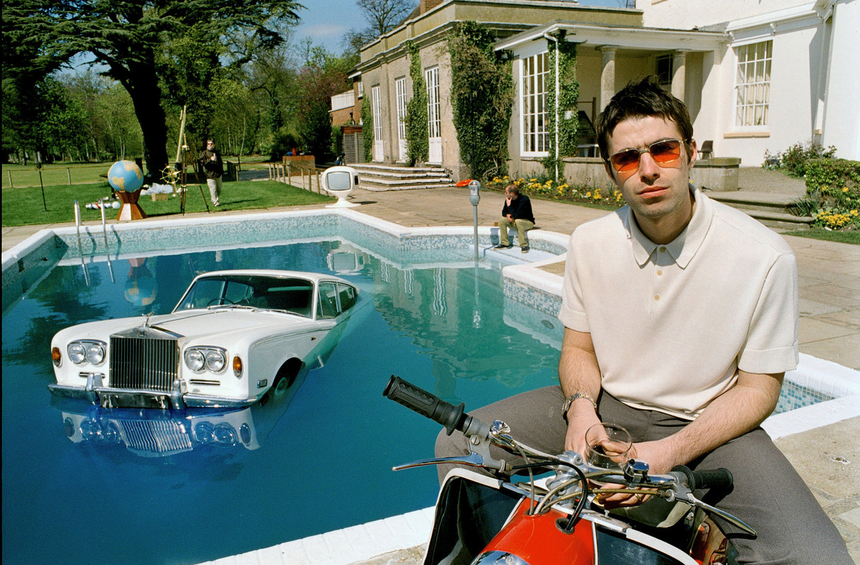 Oasis-frontman Noel Gallagher poseert op de hoes van 'Be Here Now' met een verzopen Rolls-Royce.  Beeld rv