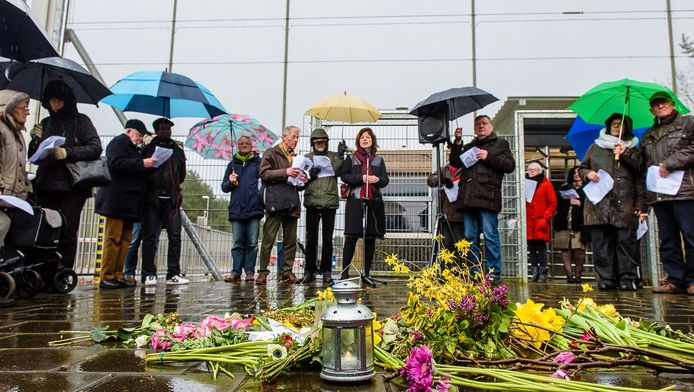Licht en bloemen voor de vluchtelingen in Kamp van Zeist. Naaflop van de wake werden bloemen aan het hek bevestigd