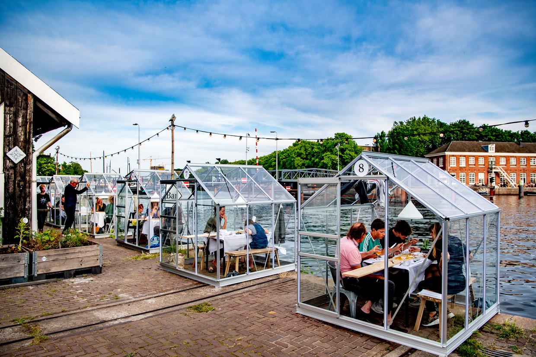 1,5 meter afstand houden bleek in de praktijk voor de nodige uitdagingen te zorgen, zo zitten gasten van dit restaurant in Amsterdam in een tuinkas. Beeld Getty