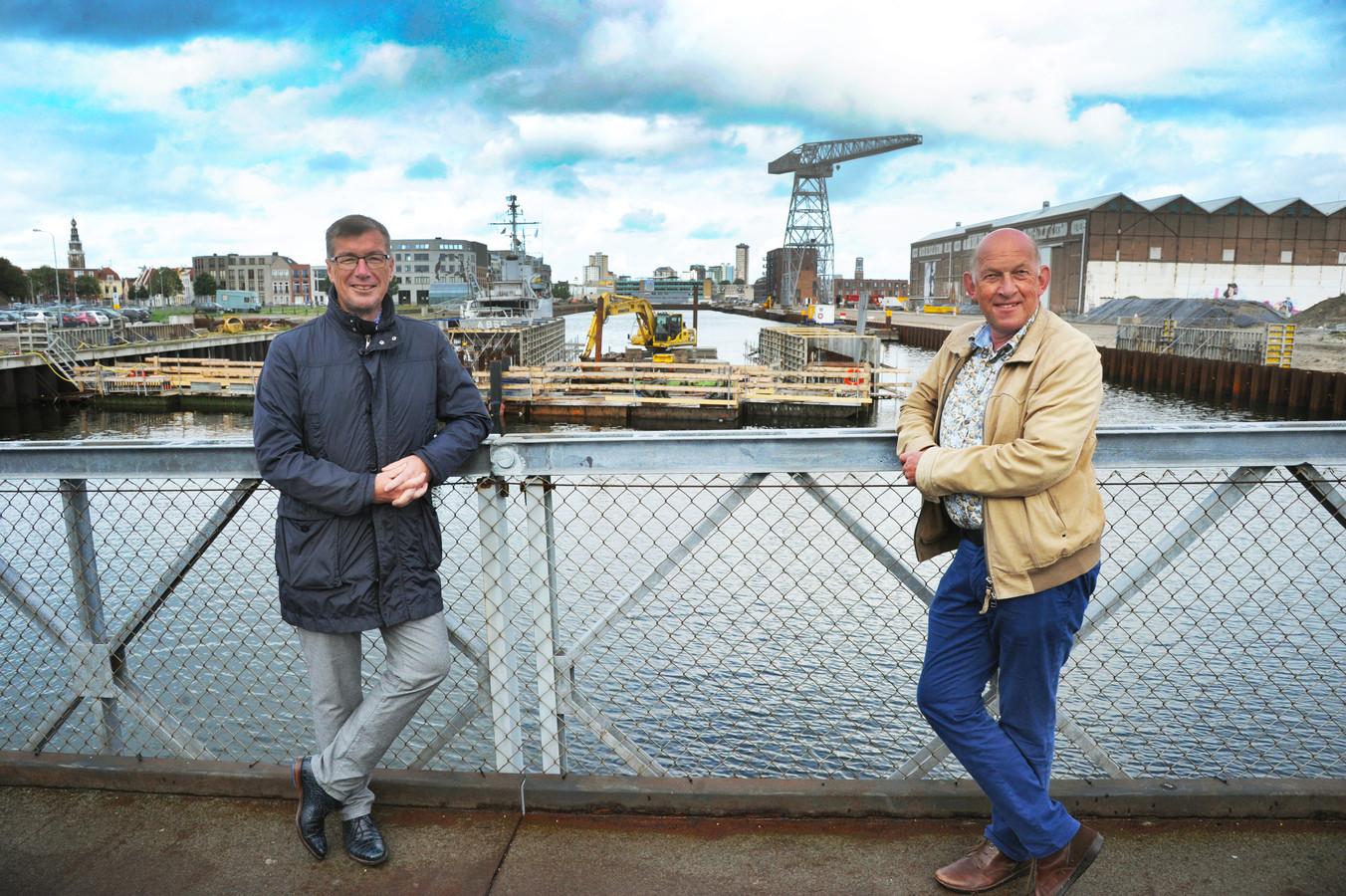 Wethouder John de Jonge (links) en projectleider Scheldekwartier Hans van Houdt staan op de huidige brug over Het Dok. Achter hen wordt gewerkt aan de nieuwe brug.
