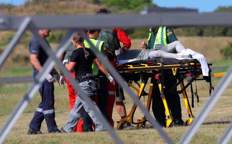 Hulpverleners bekommeren zich om een met reddingshelikopter overgebrachte gewonde op het vliegveldje van Whakatane. Beeld AP