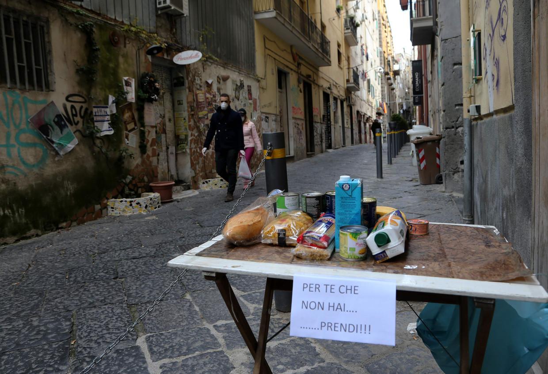 Een 'Tavolo solidare' ('solidariteitstafel') in Napels. Op het briefje staat 'Voor wie niet kan kopen... neem.' Beeld AFP