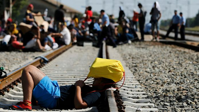 Een migrant houdt zijn tas boven zijn hoofd terwijl hij op het spoor ligt in Tovarnik, Kroatië.