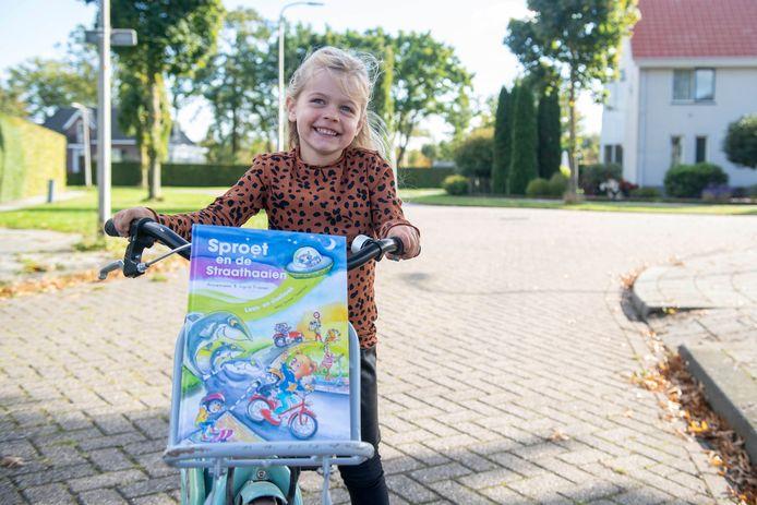 De 4-jarige Lotte Minkjan met het boek uit de verkeersveiligheidsbox op haar nieuwe fiets.