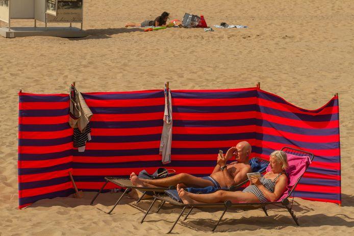 Mensen genieten van de zon aan de Belgische kust.