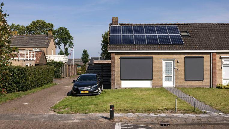 Een woning in Garyp heeft een laadpaal-combo met zonnepanelen en een elektrische auto op het gras in de tuin die aan het opladen is. Beeld Hollandse Hoogte / Ramon van Flymen