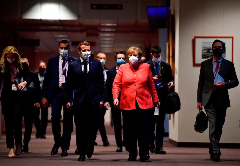 Angela Merkel en Emmanuel Macron arriveren bij een gezamenlijke persconferentie nadat een Europees akkoord is gesloten over noodhulp. Dat onder meer Nederland zo dwars lag bij de onderhandelingen, beviel beide leiders niet. Beeld AFP
