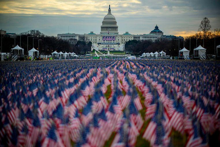 Vlaggen in plaats van toehoorders voor het Capitool in Washington.  Beeld AFP