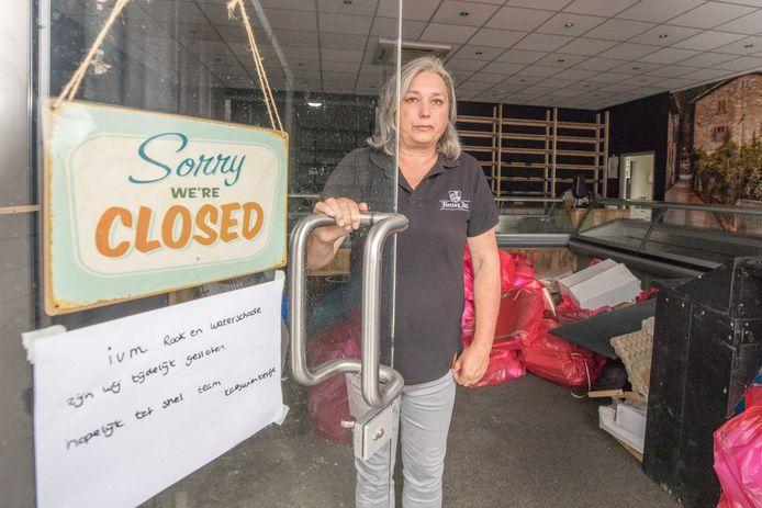 Sabina Mulders in de deuropening van haar gesloten winkel. Binnen is het een puinhoop.