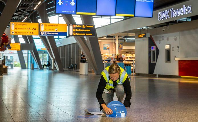 Een werkneemster van Eindhoven Airport plakt stickers op de grond die de 'corona-looproute' aangeven.