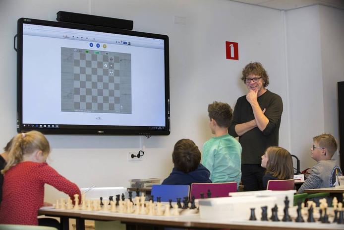 De schaakjeugd krijgt les van Niels van der Mark (staand). Foto Theo Kock