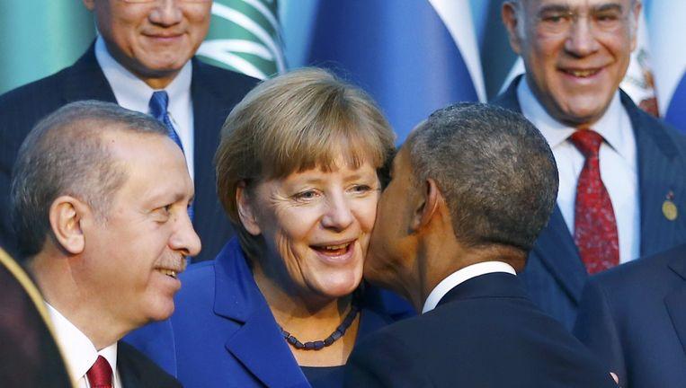Barack Obama zoent Angela Merkel op de G20-top. Beeld reuters