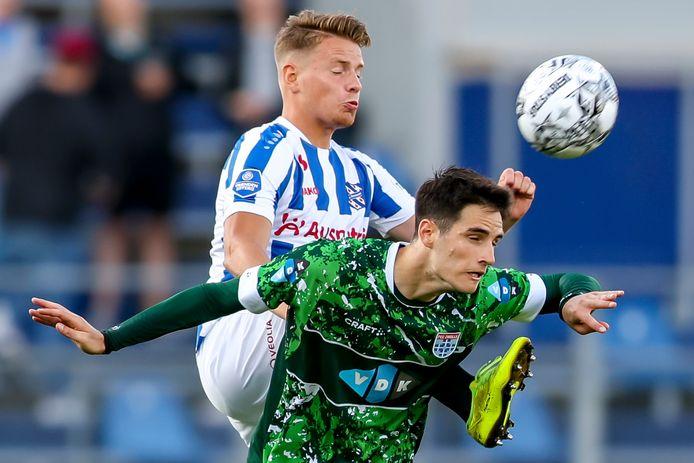 Heerenveen-speler Syb van Ottele is PEC Zwolle-spits Slobodan Tedic de baas in een luchtduel.